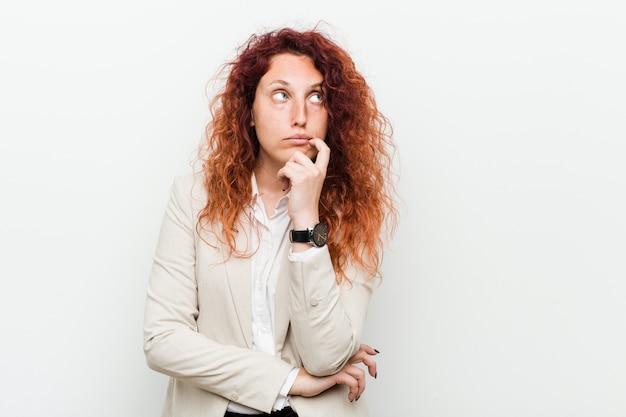 疑わしいと懐疑的な表現で横に探している若い自然な赤毛ビジネス女性。