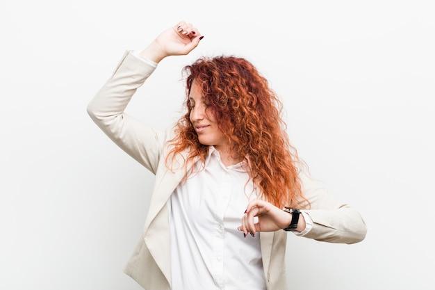 特別な日を祝っている若い自然な赤毛ビジネス女性、ジャンプしてエネルギーで腕を上げます。