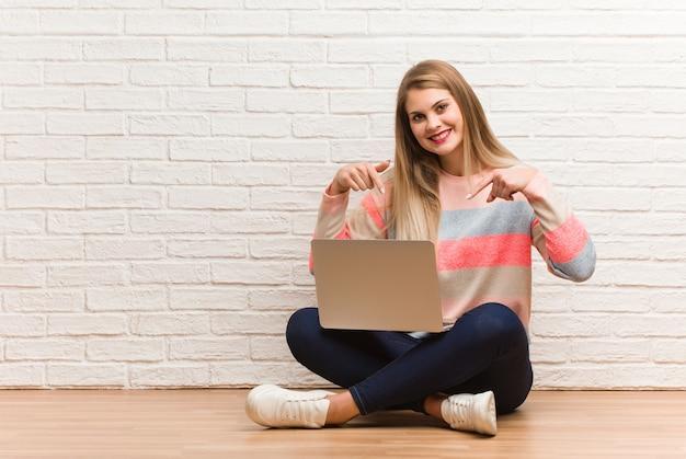 Молодой русский студент женщина сидит, указывая на дно с пальцами