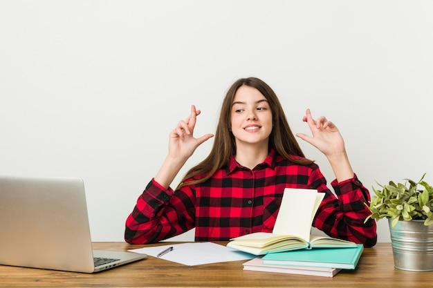 運を持っているため指を交差させる宿題をやっている彼女のルーチンに戻る若いティーンエイジャー