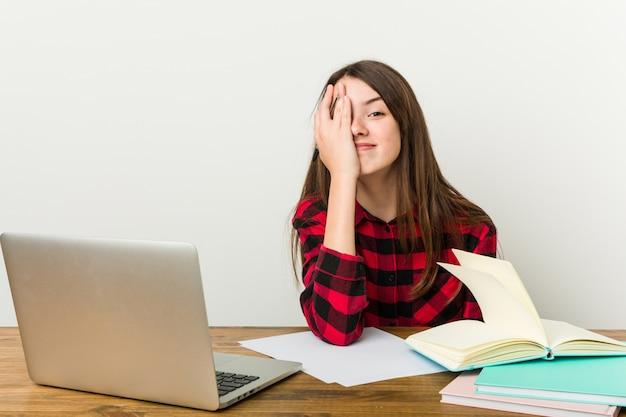 若いティーンエイジャーは宿題をやっている彼女のルーチンに戻って手のひらで顔の半分をカバーすることを楽しんで。