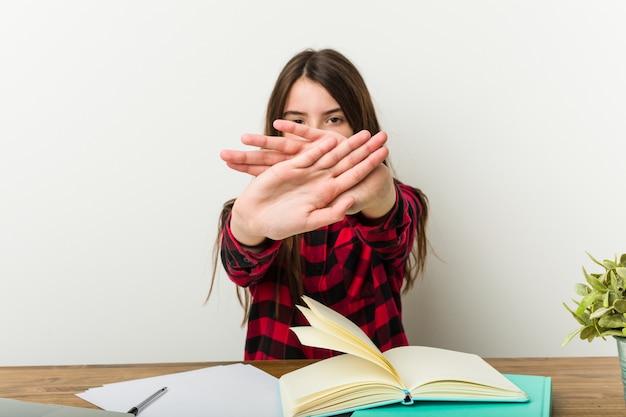 拒否のジェスチャーをしている宿題をしている彼女のルーチンに戻る若いティーンエイジャー