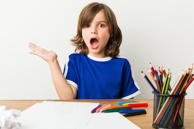 Мальчик крася и делая домашнюю работу на его впечатленном столе.