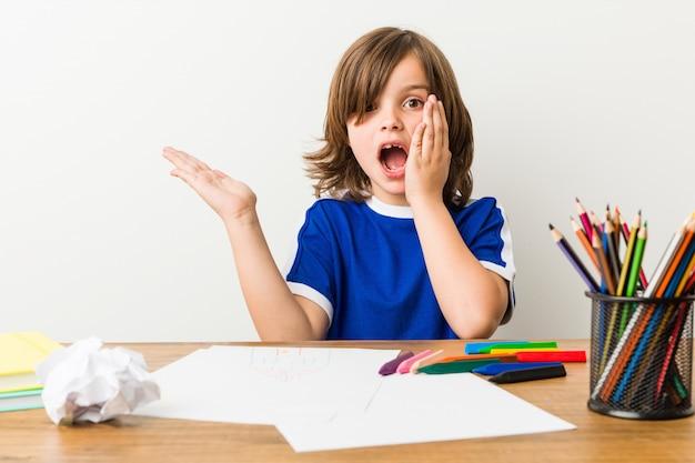 絵画と彼の机の上の宿題をやっている小さな男の子は、手のひらにコピースペースを保持しています。