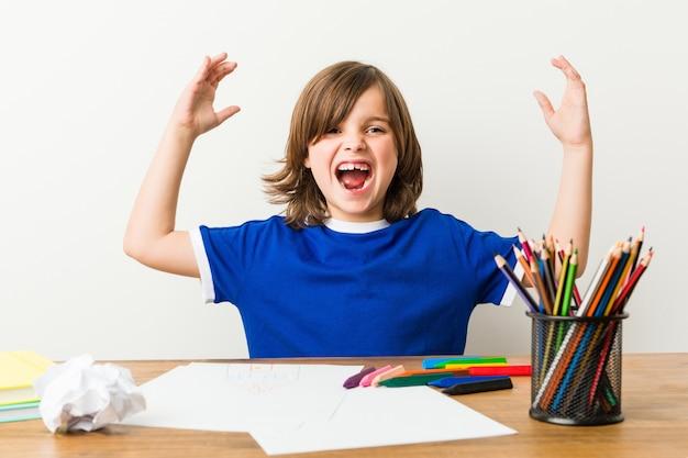 Мальчик крася и делая домашнюю работу на его столе получая приятный сюрприз.