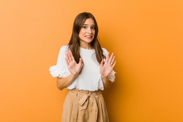 Молодая кавказская женщина отвергая кто-то показывая жест отвращения.