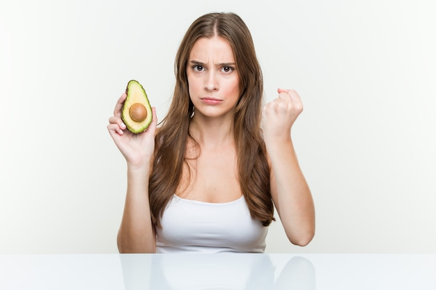 Молодая кавказская женщина держа авокадо показывая кулак, агрессивное выражение лица.