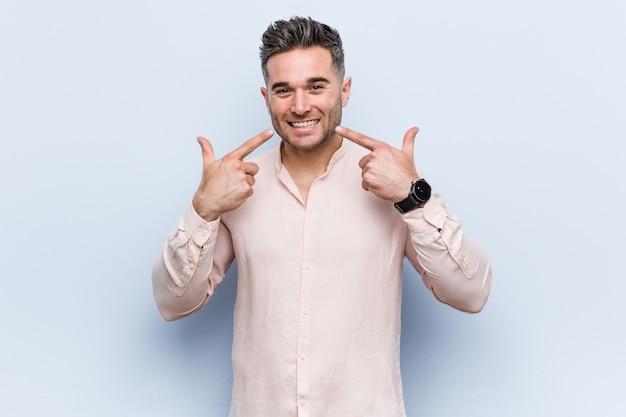 若いハンサムなクールな男の笑顔、口に指を指しています。