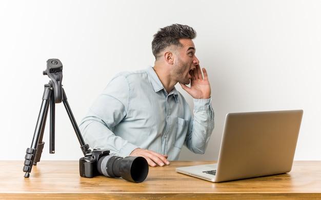 若いハンサムな写真の先生が叫び、開いた口の近くに手のひらを保持しています。