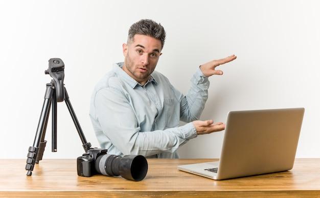 若いハンサムな写真の先生は、手の間でコピースペースを保持してショックを受け、驚いた。