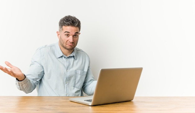 若いハンサムな男が彼のラップトップを疑って、ジェスチャーの質問で肩をすくめて作業します。
