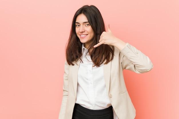 指で携帯電話のジェスチャーを示す若いブルネットビジネス女性。