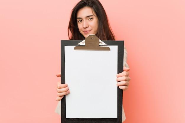 Молодая кавказская женщина держа пустую доску сзажимом для бумаги