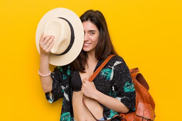Молодая кавказская женщина нося бикини и шляпу