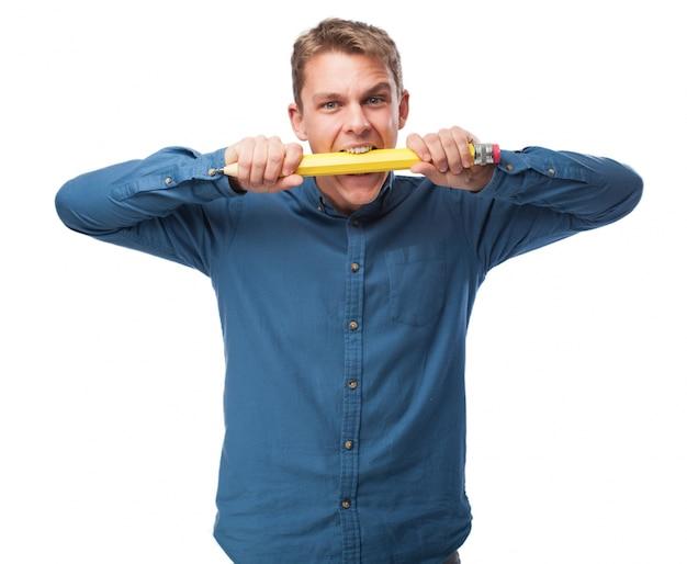 男は巨大な鉛筆をかみます
