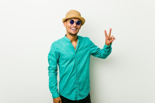勝利のサインを示し、広く笑顔の夏服を着ている若いヒスパニック男。