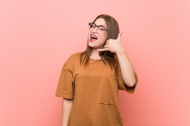 指で携帯電話のジェスチャーを示す眼鏡を着ている若い学生女性。