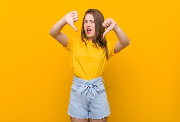 Подросток молодой женщины нося желтую рубашку показывая большой палец руки вниз и выражая нелюбовь.