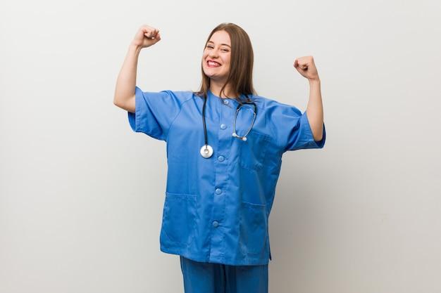 腕、女性の力で強さのジェスチャーを示す白い壁に若い看護婦さん女性