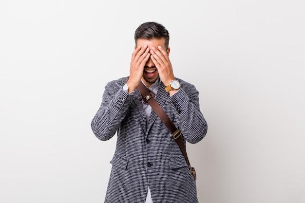 Молодой деловой филиппинский мужчина у белой стены закрывает глаза руками, широко улыбаясь в ожидании сюрприза.