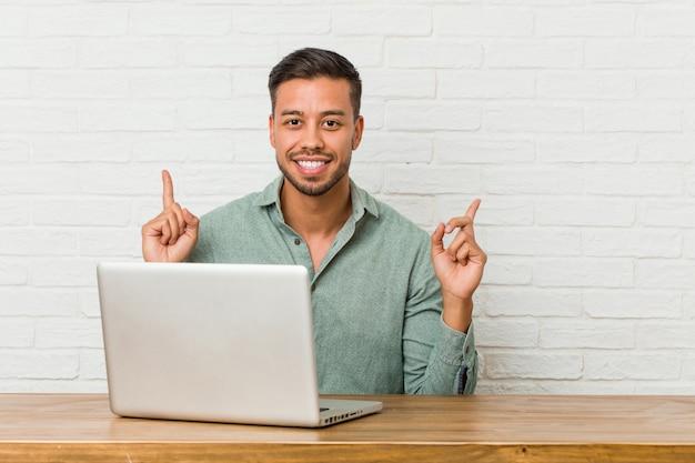 Работа молодого филиппинского человека сидя с его компьтер-книжкой показывает с обоими пальцами передней части вверх показывая пустое пространство.