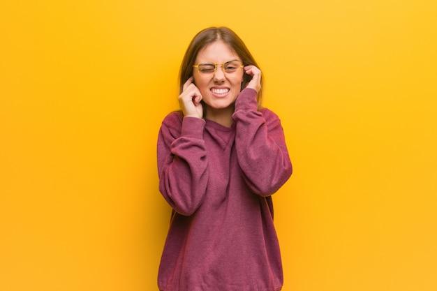 手で耳を覆う若いカジュアルな女性