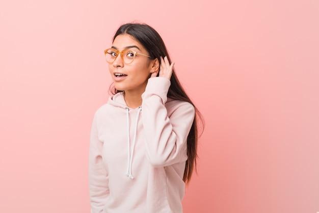 ゴシップを聴こうとしてカジュアルなスポーツの外観を着ている若いかなりアラブの女性。