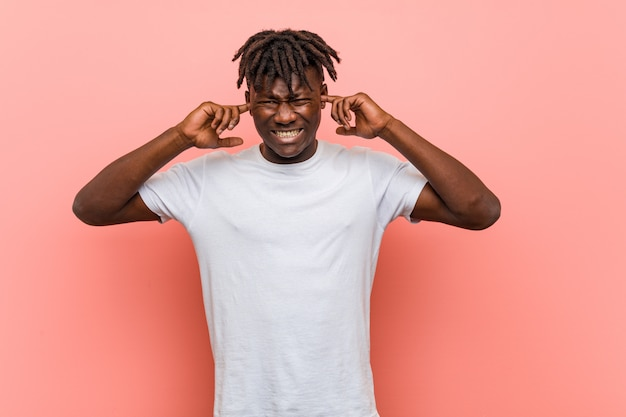 彼の手で耳を覆う若いアフリカ黒人男性。