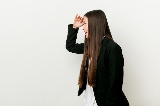 額に手を入れて遠くを見て若いかなり中国のビジネス女性。