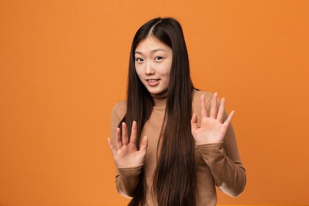 Молодая милая китайская женщина отвергая кто-то показывая жест отвращения.