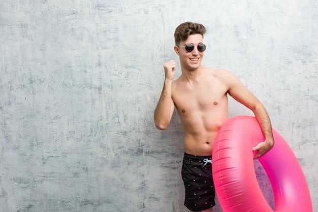 Молодой человек, держащий розовый надувной пончик носить купальник, танцы и развлечения.