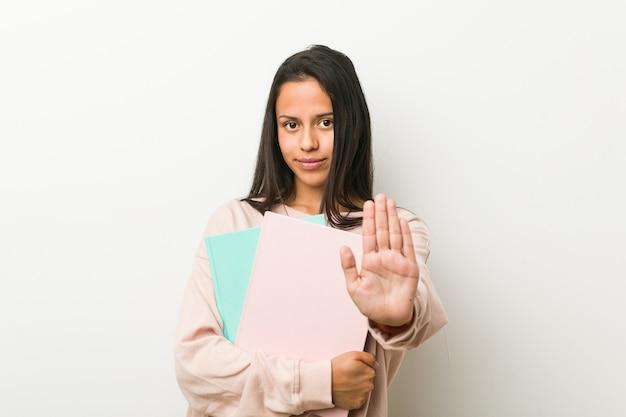 一時停止の標識を示す伸ばした手で立っているいくつかのノートを保持している若いヒスパニック系女性。
