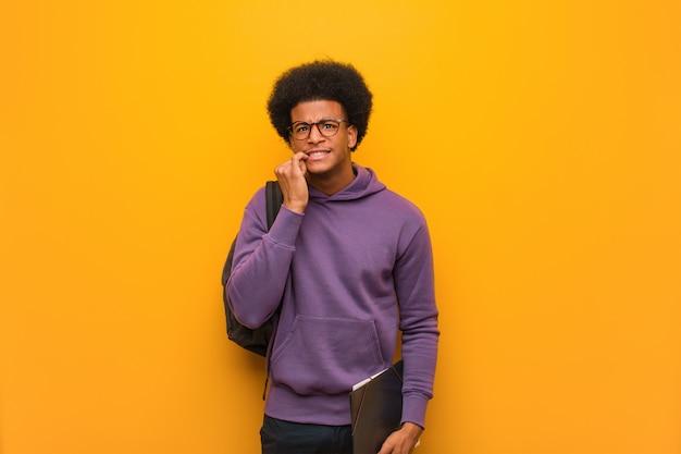 Молодой афроамериканец студент человек кусает ногти, нервный и очень беспокоиться