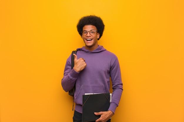 若いアフリカ系アメリカ人学生の男が驚いて、成功と繁栄を感じています