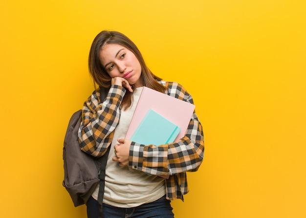 何かを考えて、側にいる若い学生女性