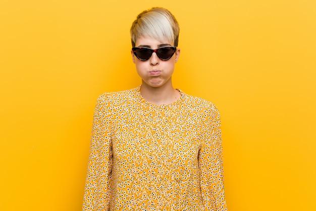 Молодая соблазнительная женщина, одетая в летнюю цветочную одежду, дует в щеки, утомленное выражение лица. концепция выражения лица.