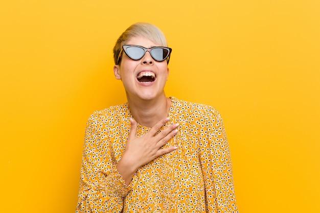 Молодая соблазнительная женщина в цветочной летней одежде громко смеется, держа руку на груди.