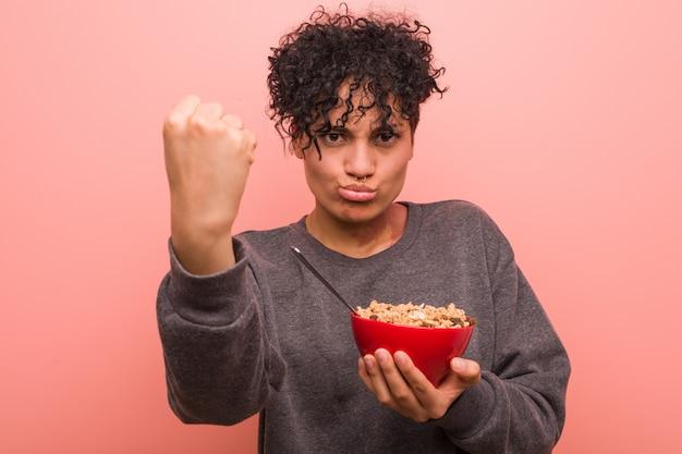 Молодая афро-американская женщина держа шар хлопьев показывая кулак, агрессивное выражение лица.