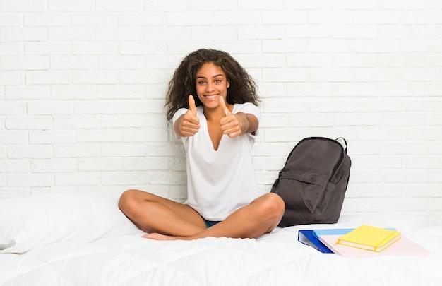 Молодая афро-американская женщина студента на кровати с большими пальцами руки поднимает, восклицает о что-то, концепции поддержки и уважения.