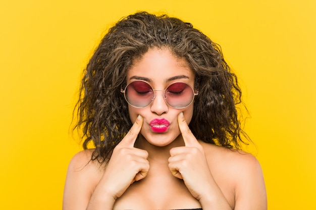 サングラスをかけている若いアフリカ系アメリカ人の美しいとメイクアップ女性のクローズアップ