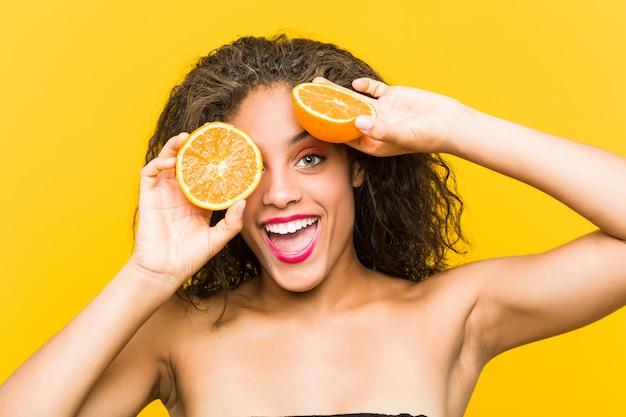 グレープフルーツを保持している若いアフリカ系アメリカ人の美しいとメイクアップ女性のクローズアップ