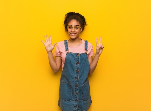 Молодая черная афроамериканская девушка с голубыми глазами показывает номер семь