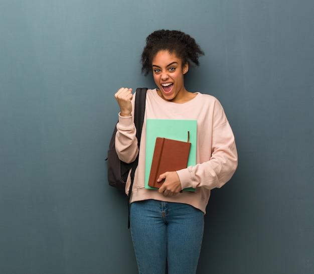 若い学生の黒人女性は驚き、ショックを受けた。彼女は本を持っています。