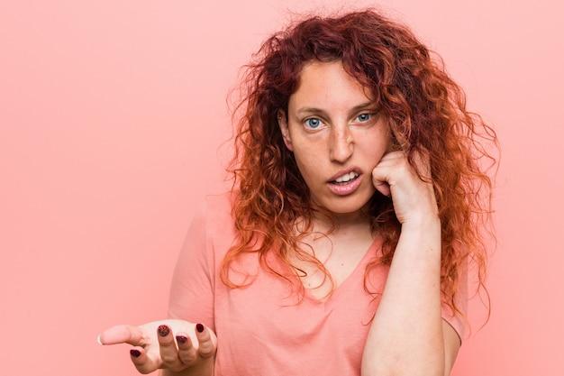 人差し指で失望のジェスチャーを示す若い自然で本物の赤毛の女性。