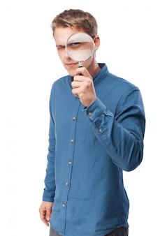 Человек смотрит через увеличительное стекло
