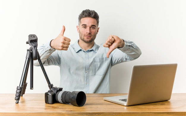 Молодой красивый учитель фотографии показывает палец вверх и вниз, трудно выбрать