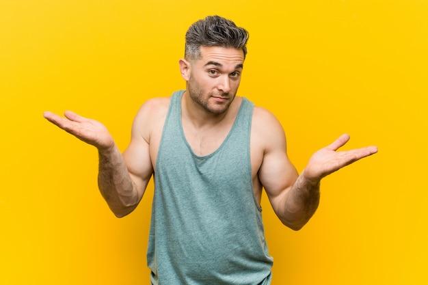 ジェスチャーを疑って肩をすくめて、肩をすくめて黄色に対する若いフィットネス男。