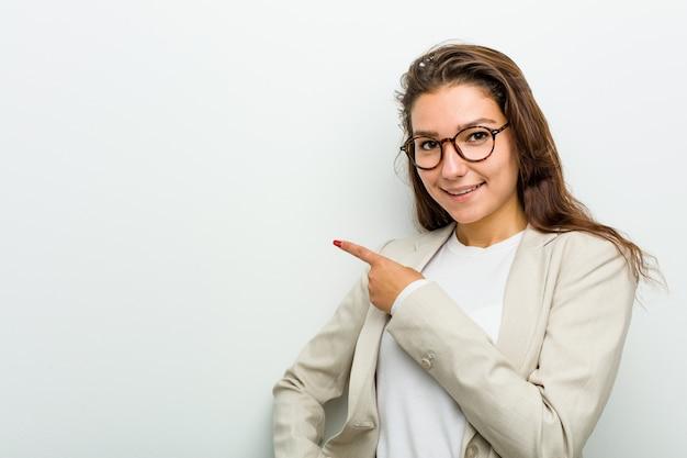 空白スペースで何かを見せて笑顔とさておき、若いヨーロッパビジネス女性。