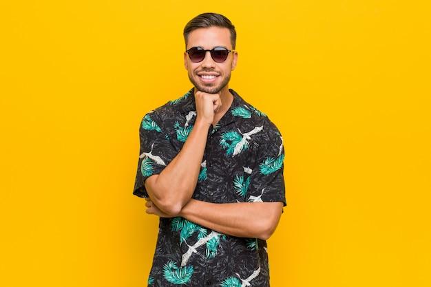 Молодой филиппинский человек в летней одежде улыбается счастливым и уверенным, касаясь подбородка рукой.
