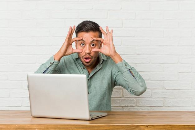 Молодой филиппинский человек, сидящий с его ноутбуком, держащим глаза, открыл, чтобы найти возможность успеха.